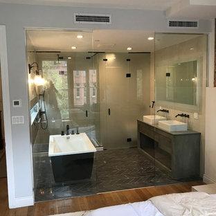Свежая идея для дизайна: большая главная ванная комната в стиле модернизм с плоскими фасадами, серыми фасадами, отдельно стоящей ванной, душевой комнатой, бежевыми стенами, настольной раковиной, столешницей из дерева, черным полом, душем с распашными дверями, полом из керамической плитки и черной столешницей - отличное фото интерьера