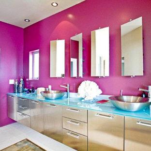 Ispirazione per una grande stanza da bagno padronale eclettica con ante lisce, pareti rosa, pavimento in gres porcellanato, lavabo a bacinella, top in vetro e pavimento grigio