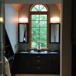 Imagen de cuarto de baño principal, tradicional renovado, de tamaño medio, con puertas de armario negras, paredes grises, lavabo bajoencimera, encimera de esteatita y suelo beige