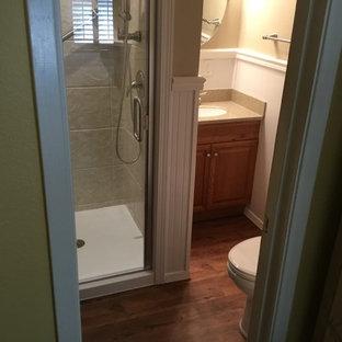Diseño de cuarto de baño con ducha, clásico, pequeño, con armarios con paneles con relieve, puertas de armario de madera oscura, ducha esquinera, paredes beige, suelo de madera oscura, lavabo bajoencimera, encimera de terrazo y ducha con puerta con bisagras