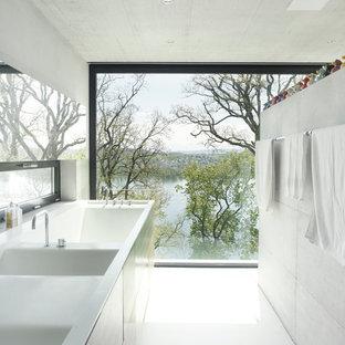 Imagen de cuarto de baño principal, minimalista, con paredes blancas, armarios con paneles lisos, puertas de armario grises, bañera encastrada, suelo de cemento y lavabo de seno grande
