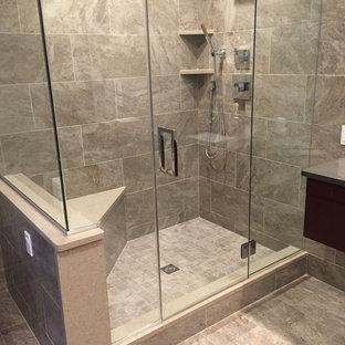 Diseño de cuarto de baño principal, minimalista, de tamaño medio, con armarios con paneles lisos, puertas de armario de madera en tonos medios, ducha empotrada, sanitario de una pieza, baldosas y/o azulejos beige, baldosas y/o azulejos grises, baldosas y/o azulejos de porcelana, paredes grises, suelo de baldosas de cerámica y encimera de acrílico