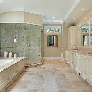 Exemple d'une grand salle de bain principale chic avec une douche d'angle, un placard à porte shaker, des portes de placard beiges, une baignoire posée, un mur beige, un sol en calcaire, un lavabo encastré, un plan de toilette en calcaire, un sol beige et une cabine de douche à porte battante.