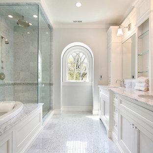 Modelo de cuarto de baño principal, tradicional renovado, grande, con bañera encastrada, ducha esquinera, paredes grises, lavabo bajoencimera, ducha con puerta con bisagras, armarios estilo shaker, puertas de armario blancas, suelo de baldosas de porcelana y encimera de mármol