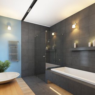 Modelo de cuarto de baño principal, minimalista, grande, con armarios con paneles lisos, puertas de armario de madera clara, ducha esquinera, sanitario de dos piezas, bañera encastrada, paredes azules, suelo de bambú, lavabo sobreencimera, encimera de madera, baldosas y/o azulejos grises, baldosas y/o azulejos de porcelana, suelo gris y ducha con puerta con bisagras