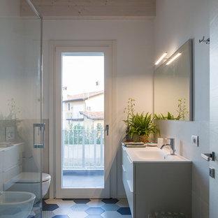 Exempel på ett modernt vit vitt badrum, med släta luckor, vita skåp, en bidé, vit kakel, vita väggar, ett integrerad handfat och flerfärgat golv