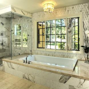 Foto de cuarto de baño principal, moderno, grande, con armarios abiertos, puertas de armario de madera en tonos medios, bañera empotrada, ducha esquinera, baldosas y/o azulejos de piedra, paredes grises, suelo de piedra caliza y encimera de granito