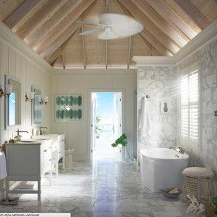 Ispirazione per una grande stanza da bagno padronale tropicale con ante in stile shaker, ante bianche, vasca freestanding, WC a due pezzi, piastrelle grigie, piastrelle di marmo, pareti beige, pavimento in marmo, lavabo da incasso, top in quarzo composito e pavimento grigio