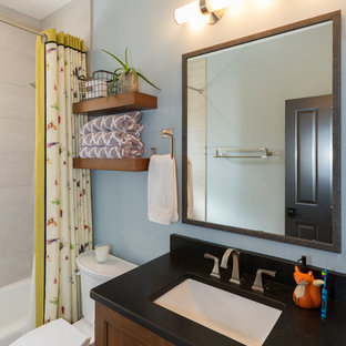 Small kids bathroom in Phoenix with recessed-panel cabinets, medium wood cabinets, an undermount tub, a shower/bathtub combo, a two-piece toilet, black and white tile, porcelain tile, blue walls, brick floors, an undermount sink, engineered quartz benchtops, red floor, a shower curtain and black benchtops.