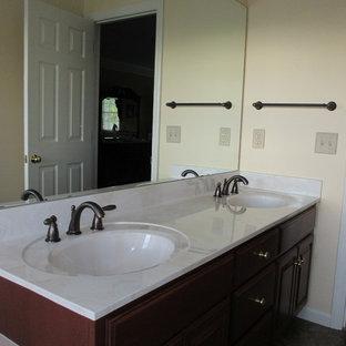 Foto de cuarto de baño principal, clásico, de tamaño medio, con lavabo integrado, armarios con paneles con relieve, puertas de armario de madera oscura, encimera de laminado, bañera esquinera, ducha empotrada, sanitario de una pieza, baldosas y/o azulejos beige, baldosas y/o azulejos de porcelana, paredes beige y suelo de linóleo