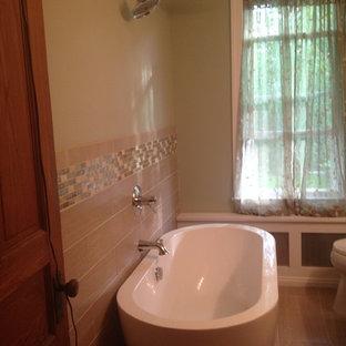 フィラデルフィアのトランジショナルスタイルのおしゃれなマスターバスルーム (シェーカースタイル扉のキャビネット、中間色木目調キャビネット、珪岩の洗面台、茶色いタイル、磁器タイル、大型浴槽、シャワー付き浴槽、一体型トイレ、アンダーカウンター洗面器、緑の壁、テラゾの床) の写真