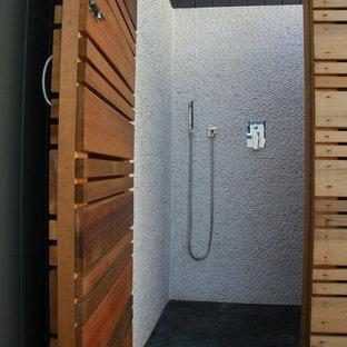 Immagine di una stanza da bagno moderna di medie dimensioni con doccia ad angolo, piastrelle bianche, piastrelle di ciottoli e pavimento in cemento