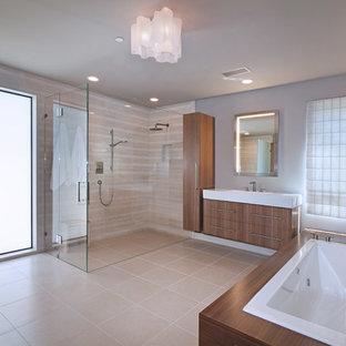 Idéer för att renovera ett 50 tals en-suite badrum, med släta luckor, skåp i mellenmörkt trä, ett platsbyggt badkar, en kantlös dusch, stenkakel, kalkstensgolv, beige kakel och grå väggar