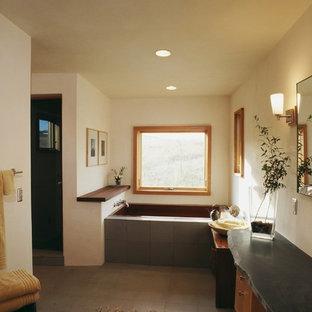 Foto de cuarto de baño principal, moderno, grande, con armarios con paneles lisos, puertas de armario de madera oscura, jacuzzi, paredes blancas, suelo de cemento, lavabo sobreencimera y encimera de cemento
