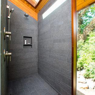 Esempio di una stanza da bagno padronale minimal di medie dimensioni con doccia a filo pavimento, piastrelle grigie, piastrelle in gres porcellanato, pareti grigie, pavimento in gres porcellanato, top in superficie solida, pavimento grigio, doccia aperta, ante lisce, ante in legno scuro e lavabo sottopiano