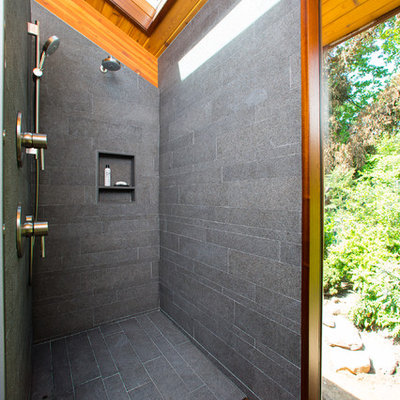 Example of a mid-sized trendy master gray tile and porcelain tile porcelain tile and gray floor bathroom design in DC Metro with gray walls, solid surface countertops, flat-panel cabinets, medium tone wood cabinets and an undermount sink