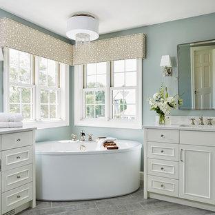 Imagen de cuarto de baño principal, clásico, de tamaño medio, con armarios con paneles empotrados, puertas de armario blancas, bañera exenta, paredes azules, suelo de baldosas de cerámica, lavabo bajoencimera, encimera de granito y suelo gris