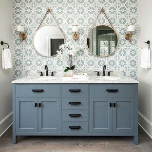 シャーロットの広いカントリー風おしゃれなマスターバスルーム (青いタイル、セメントタイル、ベージュの壁、大理石の洗面台、茶色い床、家具調キャビネット、青いキャビネット、濃色無垢フローリング、アンダーカウンター洗面器、グレーの洗面カウンター) の写真