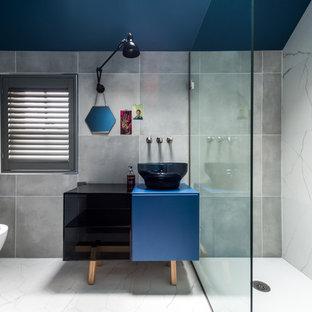 Foto di una stanza da bagno con doccia design di medie dimensioni con consolle stile comò, ante blu, doccia aperta, WC monopezzo, piastrelle grigie, lastra di pietra, pareti grigie, pavimento in gres porcellanato, lavabo a bacinella e top in laminato