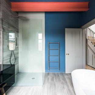 Foto de cuarto de baño infantil, contemporáneo, de tamaño medio, con armarios tipo mueble, puertas de armario grises, bañera exenta, ducha abierta, sanitario de una pieza, baldosas y/o azulejos grises, losas de piedra, paredes azules, suelo de madera clara, lavabo sobreencimera y encimera de laminado