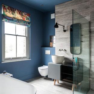 Esempio di una stanza da bagno padronale design di medie dimensioni con consolle stile comò, ante grigie, vasca freestanding, doccia aperta, piastrelle grigie, lastra di pietra, pareti blu, parquet chiaro, lavabo a bacinella, top in laminato, WC sospeso, pavimento grigio e doccia aperta