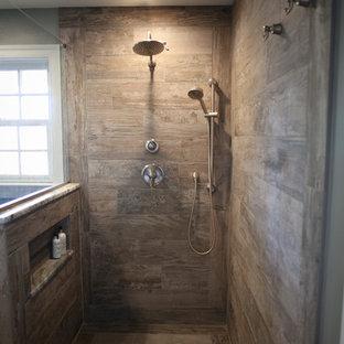 フィラデルフィアの中サイズのカントリー風おしゃれなマスターバスルーム (茶色いキャビネット、段差なし、分離型トイレ、茶色いタイル、磁器タイル、グレーの壁、磁器タイルの床、アンダーカウンター洗面器、御影石の洗面台、ベージュの床、オープンシャワー、フラットパネル扉のキャビネット) の写真