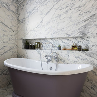 Medium sized contemporary bathroom in London with a freestanding bath, marble tiles, marble flooring, white floors and a wall niche.