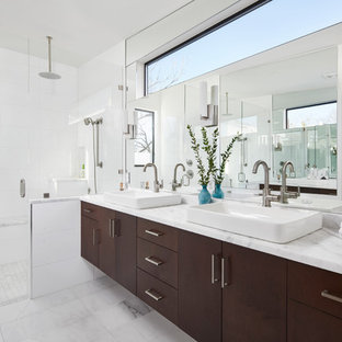 Trendy white tile white floor alcove shower photo in Austin with flat-panel cabinets, dark wood cabinets, a vessel sink, a hinged shower door and white countertops