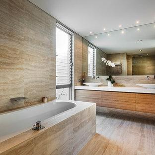 Modern inredning av ett badrum, med ett fristående handfat och travertinkakel