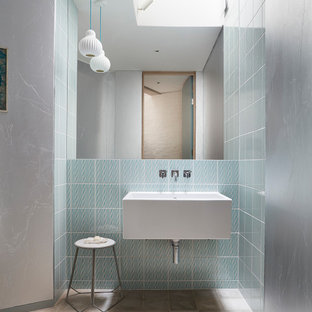 Inspiration for a mid-sized contemporary 3/4 bathroom in London with porcelain floors, a wall-mount sink, grey floor, blue tile and glass tile.