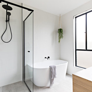 Design ideas for a scandinavian bathroom in Melbourne with a freestanding tub, white tile, white walls, a vessel sink and grey floor.