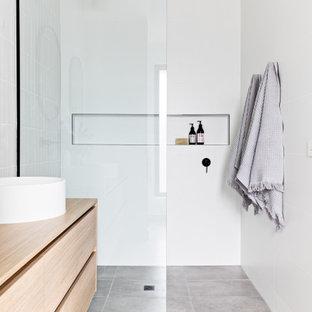 Esempio di una stanza da bagno scandinava con ante lisce, ante in legno chiaro, doccia a filo pavimento, piastrelle grigie, lavabo a bacinella, top in legno, pavimento grigio, doccia aperta e top beige