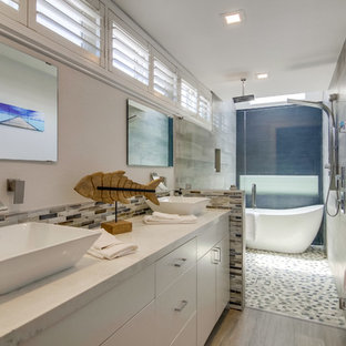 Large coastal blue tile and gray tile gray floor bathroom photo in San Diego with flat-panel cabinets, white cabinets, gray walls, a vessel sink, a hinged shower door and white countertops