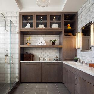 Cette photo montre une salle de bain principale chic avec un plan de toilette en marbre, un placard à porte plane, des portes de placard en bois sombre, un carrelage blanc, un carrelage métro, un mur blanc, un lavabo encastré et une cabine de douche à porte battante.