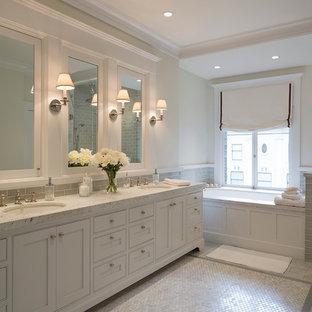 Exemple d'une salle de bain chic avec un lavabo encastré, des portes de placard blanches, une baignoire encastrée, une douche d'angle, un carrelage gris, un carrelage en pâte de verre, un sol en carrelage de terre cuite, un mur gris et un placard avec porte à panneau encastré.