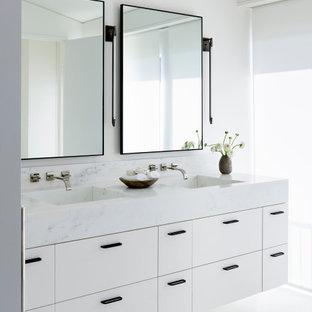 Inspiration för mycket stora moderna vitt en-suite badrum, med släta luckor, vita skåp, vita väggar, ett integrerad handfat, marmorbänkskiva och vitt golv