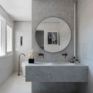 Design ideas for a large contemporary master bathroom in Sydney with a freestanding tub, white tile, stone tile, white walls, ceramic floors, an undermount sink, granite benchtops, white floor and white benchtops.