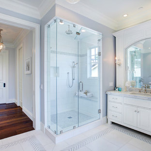 Inspiration for a timeless white tile corner shower remodel in Los Angeles with an undermount sink, raised-panel cabinets, white cabinets and gray walls
