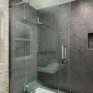 Esempio di una piccola stanza da bagno padronale minimalista con lavabo integrato, ante lisce, ante in legno bruno, top in quarzo composito, vasca da incasso, vasca/doccia, WC sospeso, piastrelle nere, piastrelle di cemento, pareti grigie e pavimento con piastrelle in ceramica