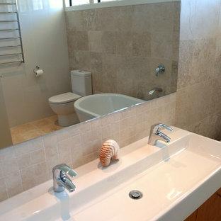 Ispirazione per una grande stanza da bagno padronale moderna con vasca freestanding, ante in legno scuro, piastrelle in travertino, pavimento in marmo e lavabo rettangolare