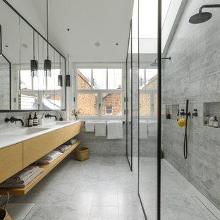 Exemple d'une très grand salle de bain principale tendance avec un placard à porte plane, des portes de placard en bois clair, une douche à l'italienne, un carrelage gris, un lavabo encastré, un sol gris, aucune cabine, un plan de toilette blanc, meuble double vasque et meuble-lavabo suspendu.
