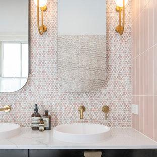 Inredning av ett modernt stort vit vitt en-suite badrum, med möbel-liknande, svarta skåp, ett fristående badkar, en öppen dusch, en vägghängd toalettstol, rosa kakel, mosaik, rosa väggar, klinkergolv i keramik, ett fristående handfat, marmorbänkskiva, svart golv och med dusch som är öppen