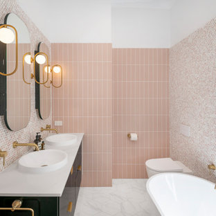 Large contemporary master bathroom in Brisbane with furniture-like cabinets, black cabinets, a freestanding tub, an open shower, a wall-mount toilet, pink tile, mosaic tile, pink walls, ceramic floors, a vessel sink, marble benchtops, black floor, an open shower, white benchtops, a niche, a double vanity and a floating vanity.