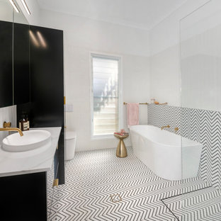 Design ideas for a large contemporary kids bathroom in Brisbane with furniture-like cabinets, black cabinets, a freestanding tub, an open shower, a wall-mount toilet, black and white tile, ceramic tile, white walls, ceramic floors, a vessel sink, marble benchtops, black floor, an open shower, white benchtops, a single vanity and a floating vanity.