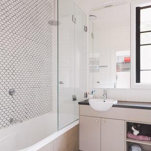 Foto di una stanza da bagno padronale minimalista di medie dimensioni con ante a filo, ante grigie, vasca ad angolo, vasca/doccia, piastrelle bianche, piastrelle in ceramica, pareti bianche, pavimento con piastrelle in ceramica, lavabo integrato e top alla veneziana
