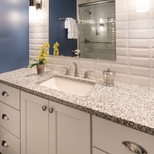 Alcove shower - small transitional kids' white tile and ceramic tile porcelain floor alcove shower idea in Charlotte with an undermount sink, white cabinets, granite countertops, a two-piece toilet, blue walls and recessed-panel cabinets