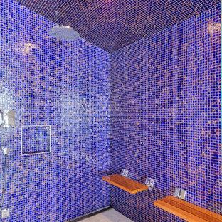 Modern inredning av ett mycket stort badrum, med blå kakel, flerfärgad kakel, släta luckor, bruna skåp, ett fristående badkar, en kantlös dusch, en vägghängd toalettstol, glaskakel, grå väggar, ljust trägolv, ett undermonterad handfat och granitbänkskiva