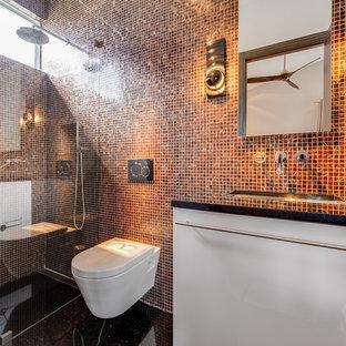 Foto de cuarto de baño con ducha, actual, con ducha a ras de suelo, sanitario de pared, baldosas y/o azulejos naranja, baldosas y/o azulejos multicolor, encimera de acrílico, armarios con paneles lisos, puertas de armario blancas, baldosas y/o azulejos en mosaico, lavabo bajoencimera y ducha abierta