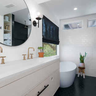 Example of a small beach style master black and white tile and ceramic tile porcelain floor, black floor and double-sink bathroom design in Other with flat-panel cabinets, light wood cabinets, a two-piece toilet, white walls, an undermount sink, quartz countertops, a hinged shower door, white countertops, a niche and a floating vanity
