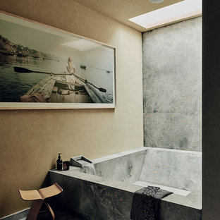 This is an example of a world-inspired bathroom in London with an alcove bath, a shower/bath combination, grey tiles, beige walls, grey floors and an open shower.